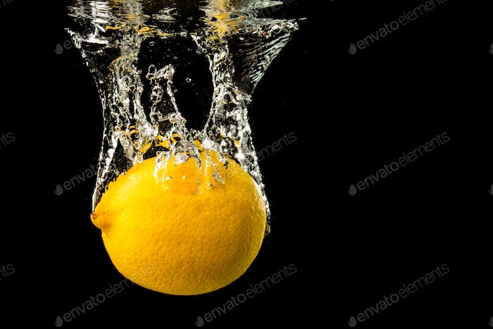 Fresh yellow lemon in water splash on black background with lots of air bubbles.