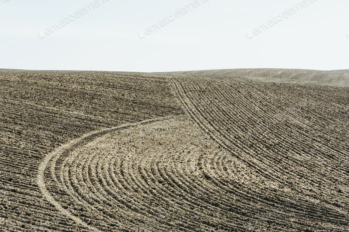 Ploughed earth furrows, patterns on the surface of the soil on farmland