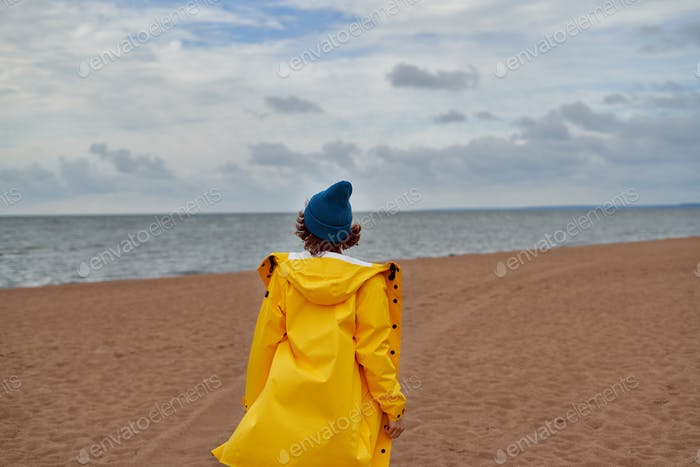 Back view of woman in bright yellow cloak and red hat on shore of North sea on autumn day