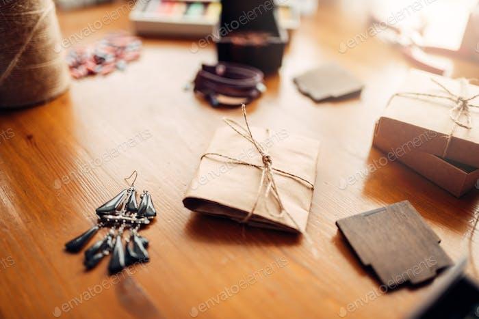 Geschenkbox und handgefertigte Ohrringe auf Holztisch