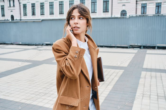 Stylish businesswoman in coat with laptop talking on cellphone thoughtfully looking away