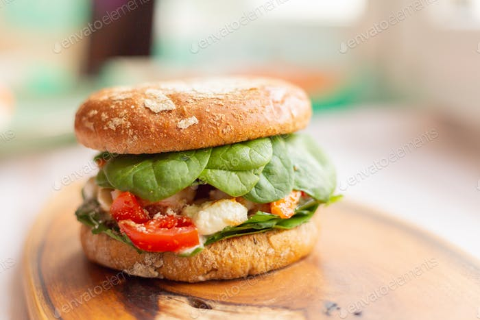 Burger with king prawn, feta cheese and vegetables, on a wooden board