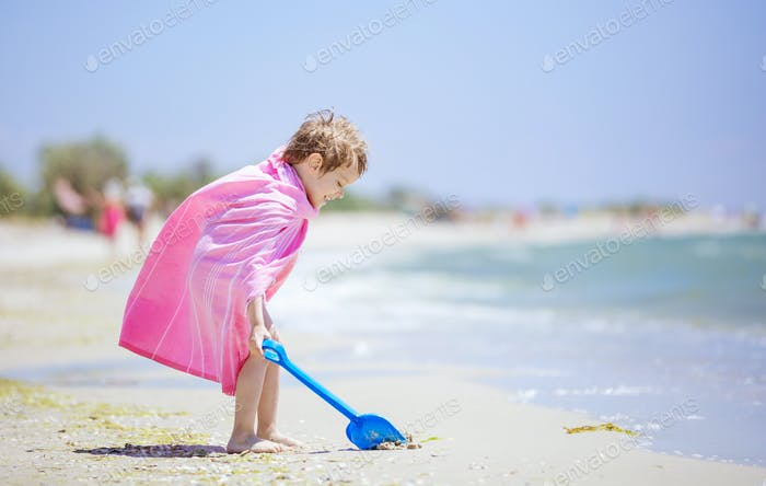 Happy boy in beach towel playing with shovel