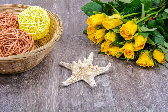 Starfish, gift and roses on a wooden table