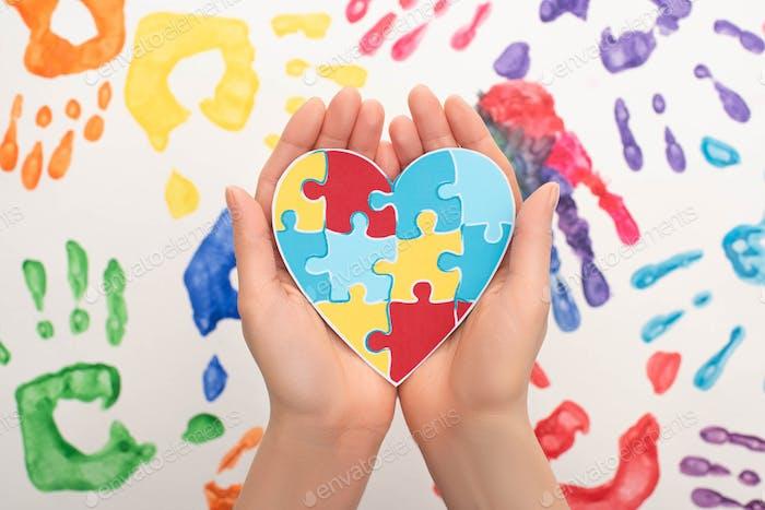 abgeschnittene Ansicht einer Frau mit Herz und Puzzle auf Weiß mit Handabdrücken für Welt-Autismus-Bewusstsein