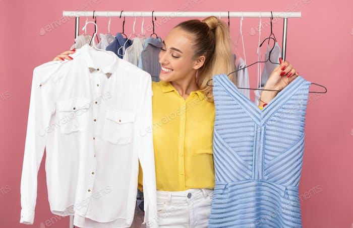 Junge Dame hält Kleiderbügel mit Kleid und Hemd