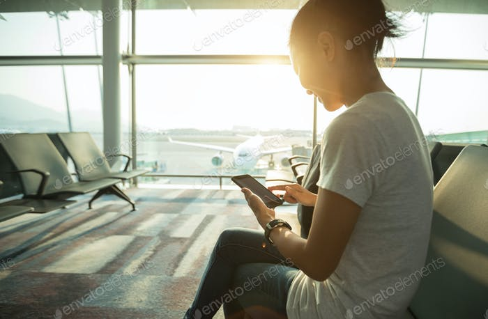 Woman traveller using cellphone in airport