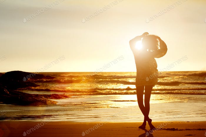 Silhouette of young woman walking on beach from behind