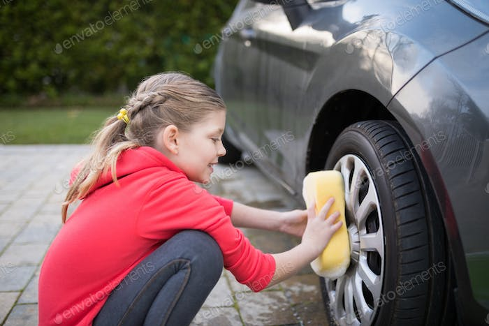 Teenage girl washing a car on a sunny day