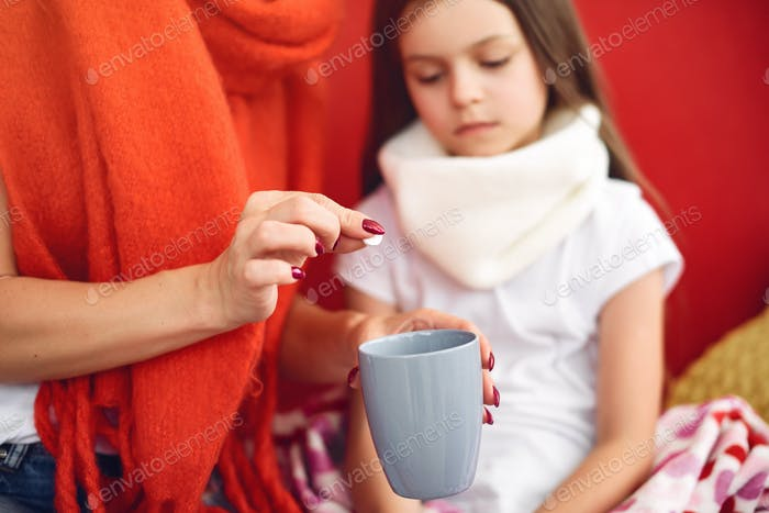 Mother gives her sick daughter hot tea