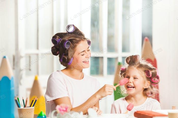 Kleines Mädchen sitzen mit ihrer Mutter und Essen Eis