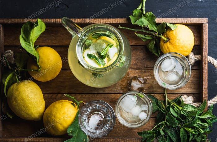 Jug and glasses with homemade lemonade, ice cubes on wooden tray, top view