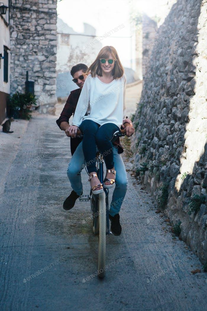 Laughing couple riding bike