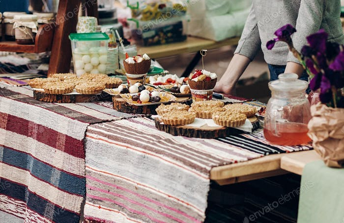 Tasty cookies and cakes with creamy cupcakes on table