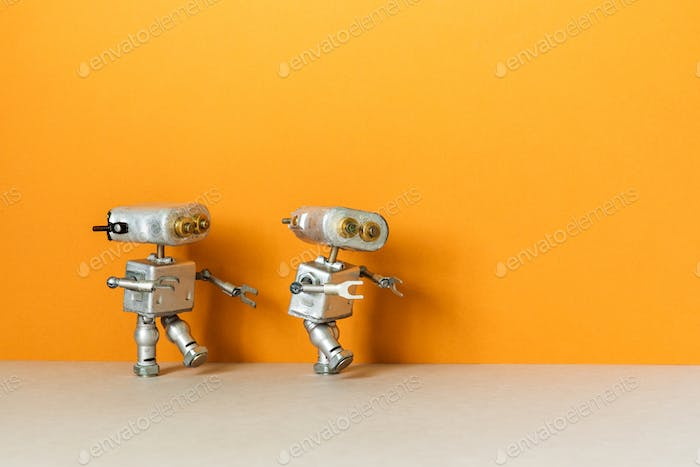 Two metal silver robots on an orange background