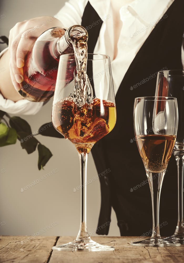 Sommelier pouring rose wine into glass at wine tasting in winery, bar or restaurant