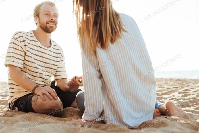 Loving couple sitting outside at the beach