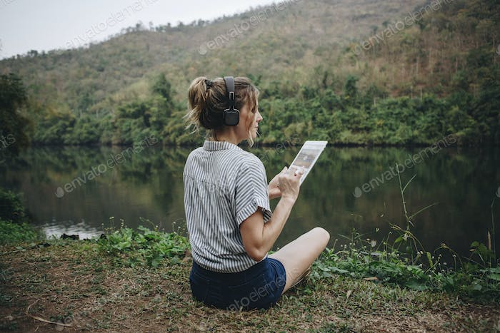 Woman in nature listening to music with headphones and digital tablet music