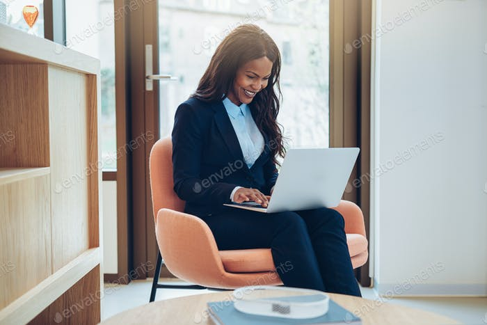 Smiling African American businesswoman using her laptop in a lounge