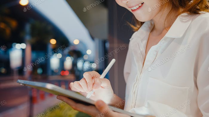 Asia businesswoman in fashion office clothes using smart pen technology for write on digital tablet.