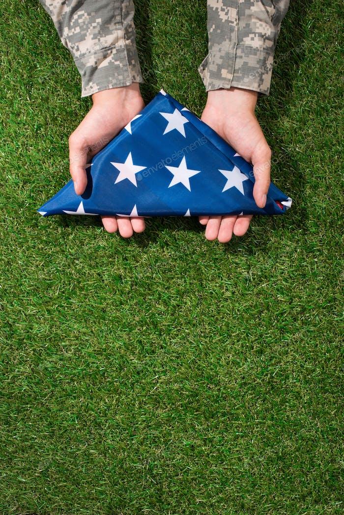 Soldat in Militäruniform hält gefaltete Flagge in Händen