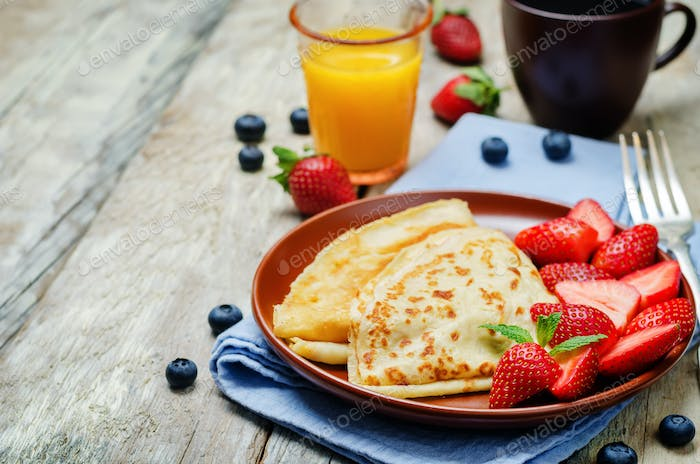 Crepes with strawberries on a wood background
