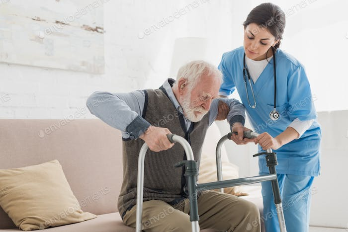Doctor helping to retired man, getting up from sofa