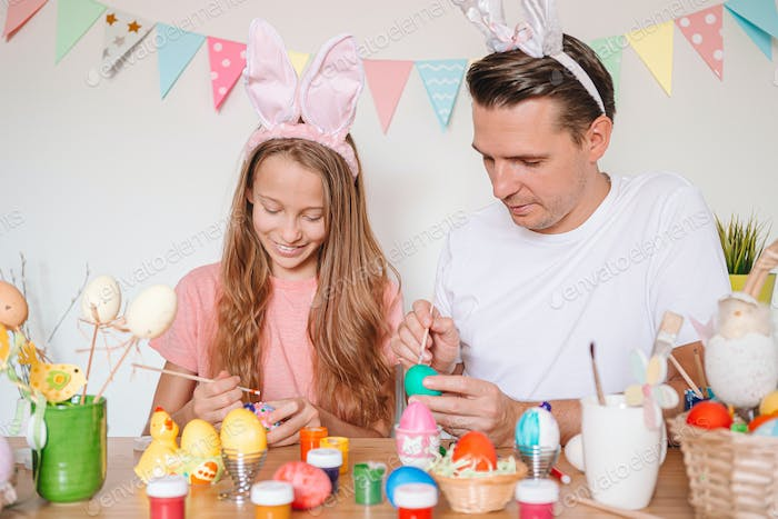 Father and his little daughter painting eggs. Happy family preparing for Easter