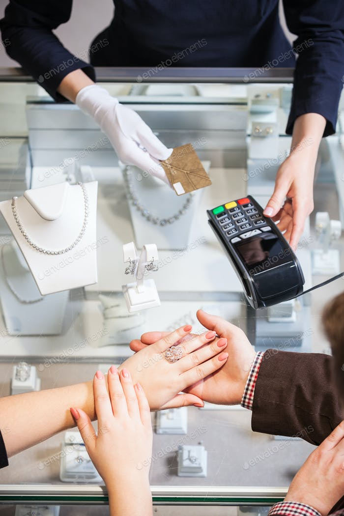 """Young woman putting on golden ring, man paying for it with credit card"