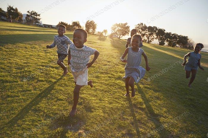 Grundschule Kinder laufen zur Kamera in einem offenen Feld