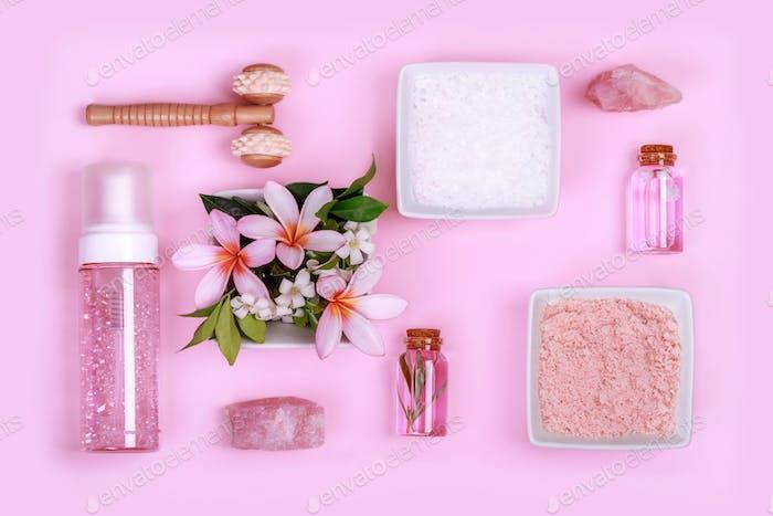 Spa-Komposition mit Schalen mit steinweißem und rosa Salz und Blumen, Kristallen, Schaumseife.