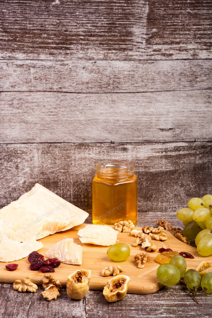 Grape, honey, different type of cheese and nuts on wooden backgr