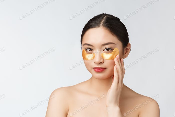 Asian beauty teenager woman care her skin with gold eye masks patches under eyes