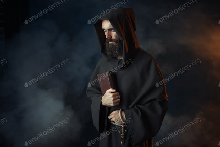Medieval monk in robe holds spellbook in hands