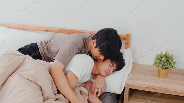 Asian Gay couple kiss and hug on bed at home.