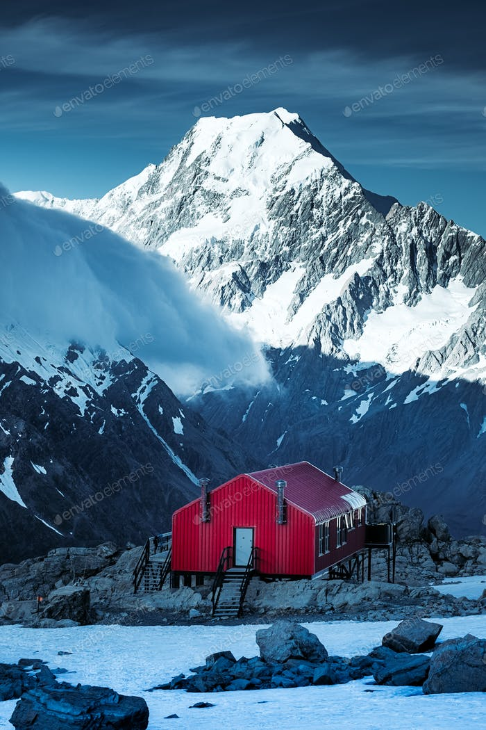 Winter landscape view of red mountain hut and Mt Cook peak, NZ