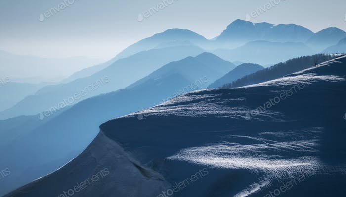 Mountain silhouettes in snowy conditions