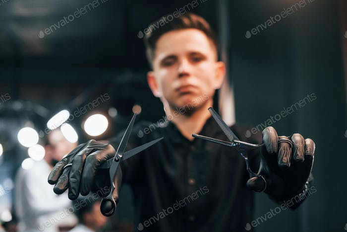 Portrait of young guy in black clothes that standing indoors in barber shop and holding scissors