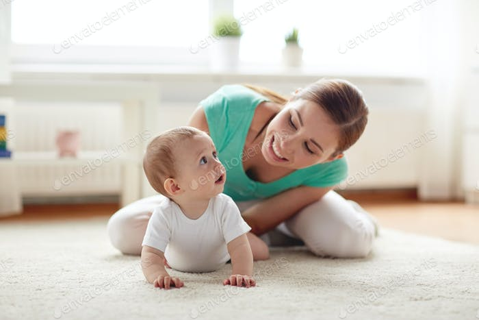 happy mother playing with baby at home
