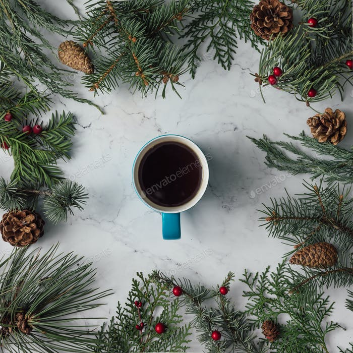 Creative arrangement of Christmas winter foliage with coffee cup. Holiday background. Flat lay.