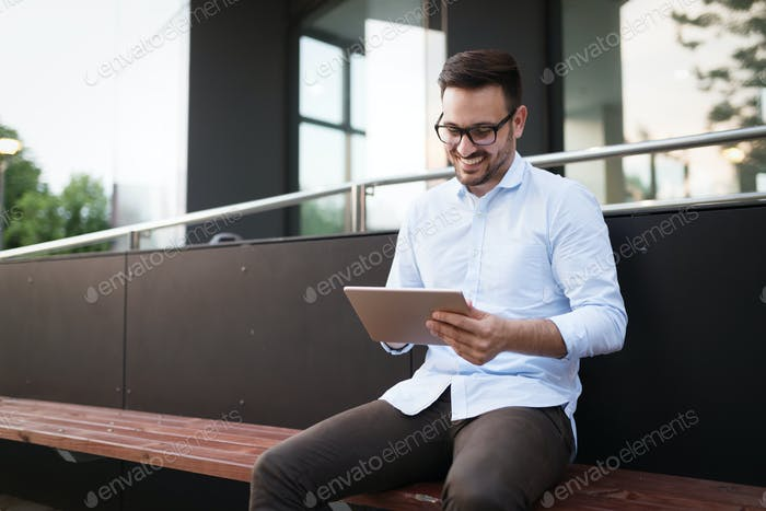 Happy and confident businessman using tablet