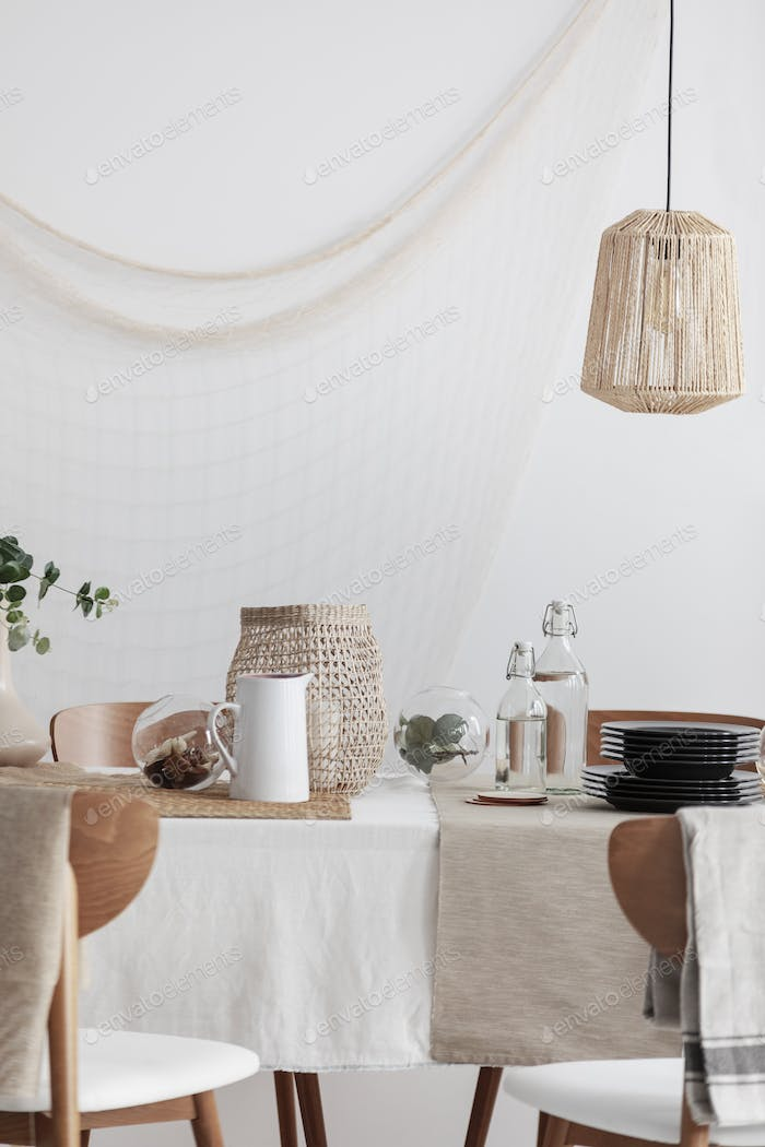 Rattan lamp above table in rustic dining room