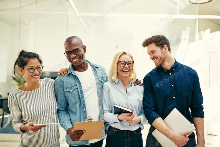 Laughing group of diverse businesspeople standing together in an office