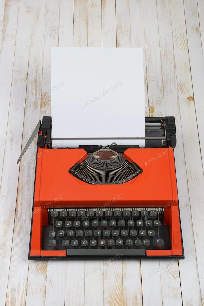 Red typewriter on white wood plank