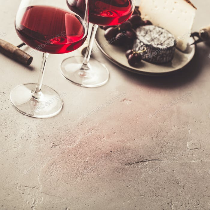 Red wine and cheese on concrete background