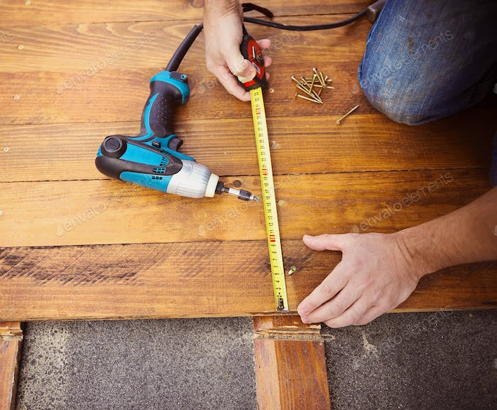 Male hands measuring wooden floor