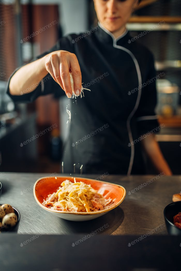 Chef cooking pasta with cheese in a bowl