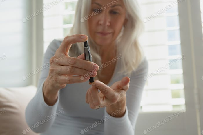 Front view of active senior Caucasian woman testing her blood sugar level with glucometer at home
