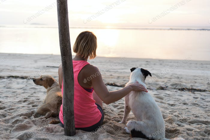 young womn or girl caressing two dogs