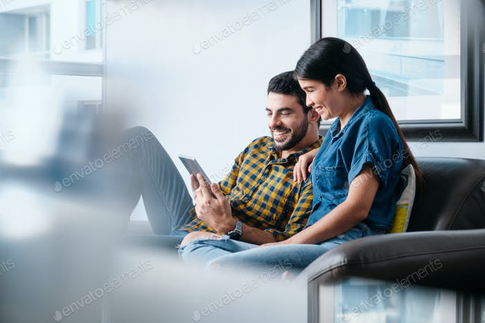 Young Couple Watching Video On Tablet.